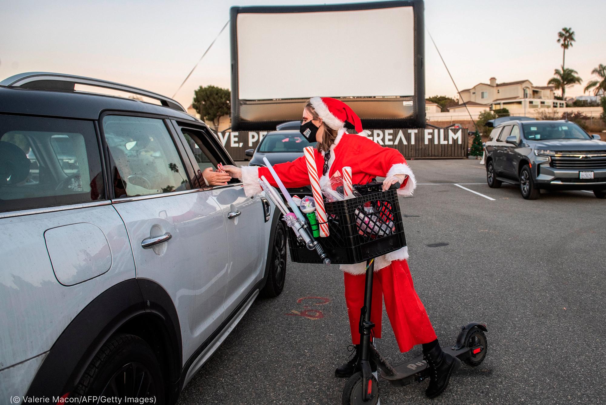 Une femme déguisée en Père Noël distribue des bonbons à des personnes dans leur voiture garée sur le parking d'un cinéma en plein air (© Valerie Macon/AFP/Getty Images)