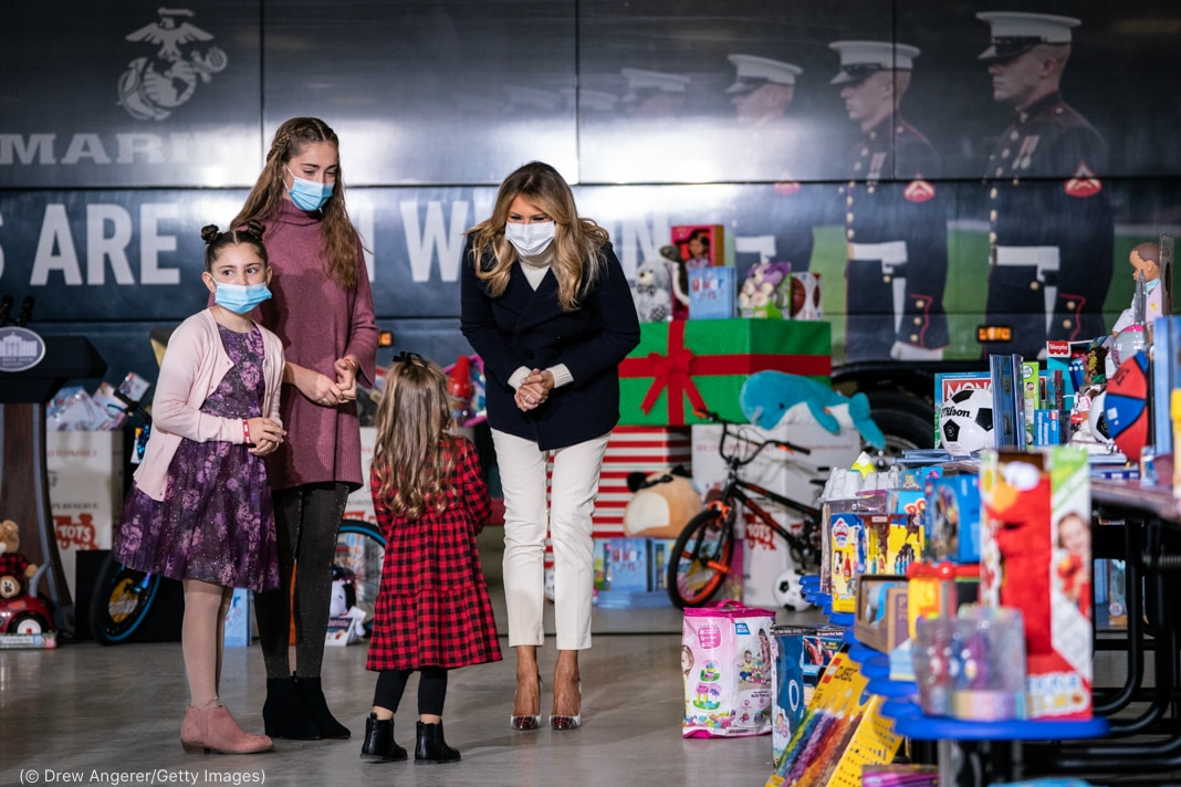 Melania Trump and three girls on stage near rows of toys (© Drew Angerer/Getty Images)