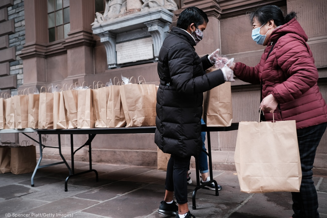 Person handing paper bag to another person standing in front of table with many paper bags (© Spencer Platt/Getty Images)