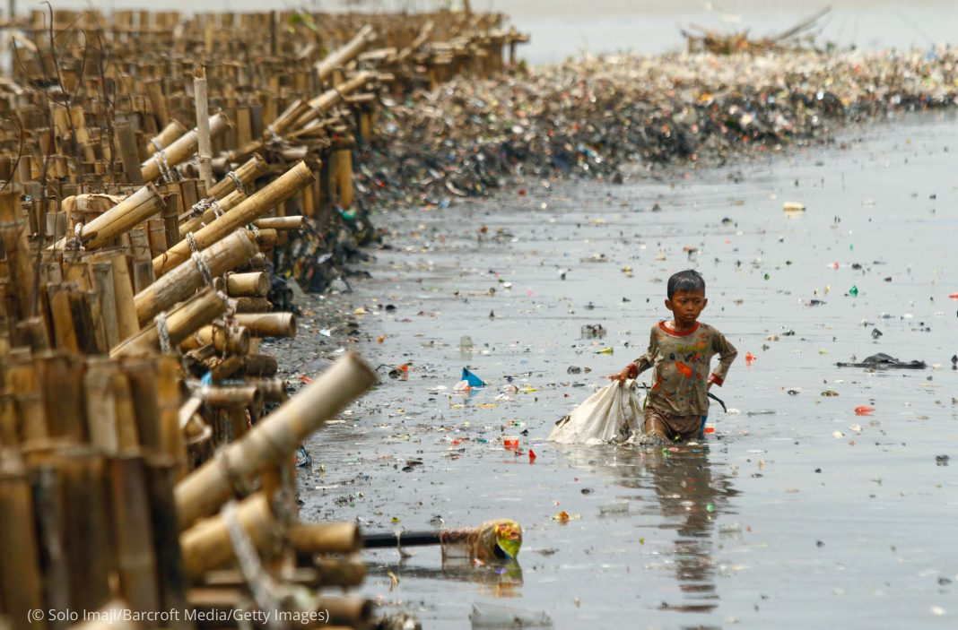 Child wading through trash-filled water while carrying bag (© Solo Imaji/Barcroft Media/Getty Images)