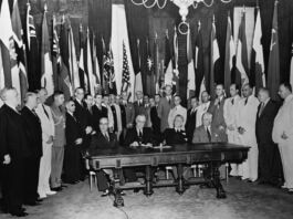Men surrounding a desk for the signing of the United Nations Declaration (© United Nations)