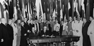 Men seated at table with others surrounding them, with various flags behind them (© Bettmann/Getty Images)