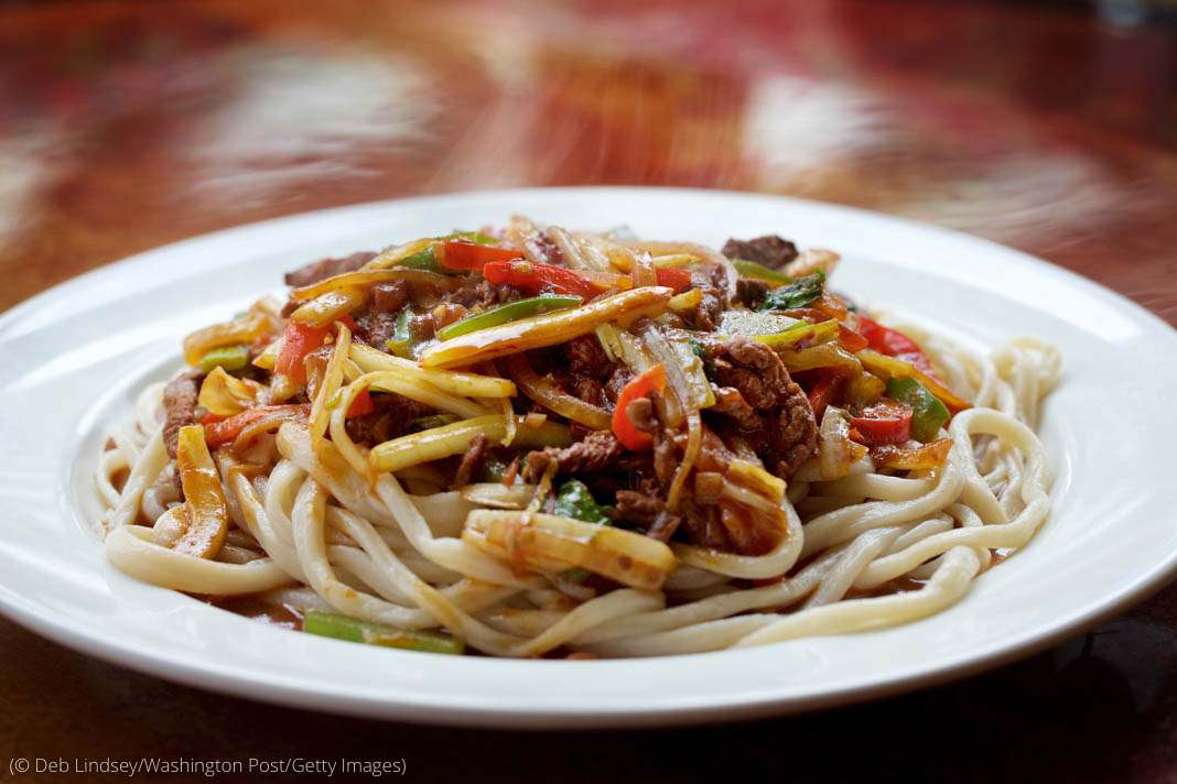 Vegetables and bits of meat over noodles on plate (© Deb Lindsey/Washington Post/Getty Images)