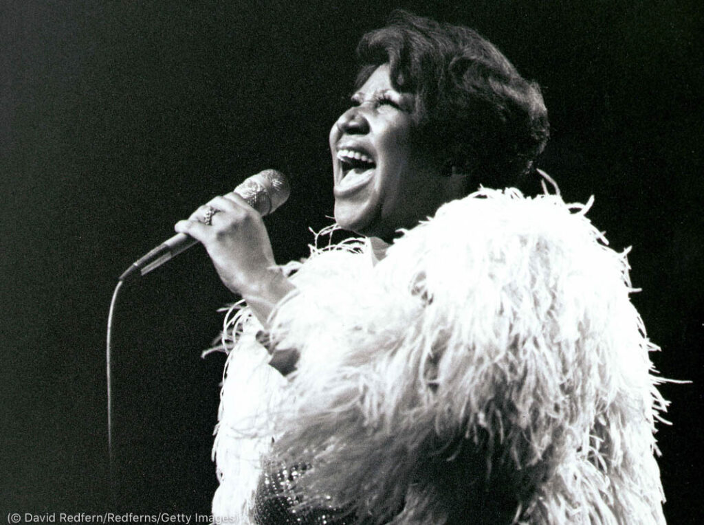 Aretha Franklin canta ante un micrófono (© David Redfern/Redferns/Getty Images)