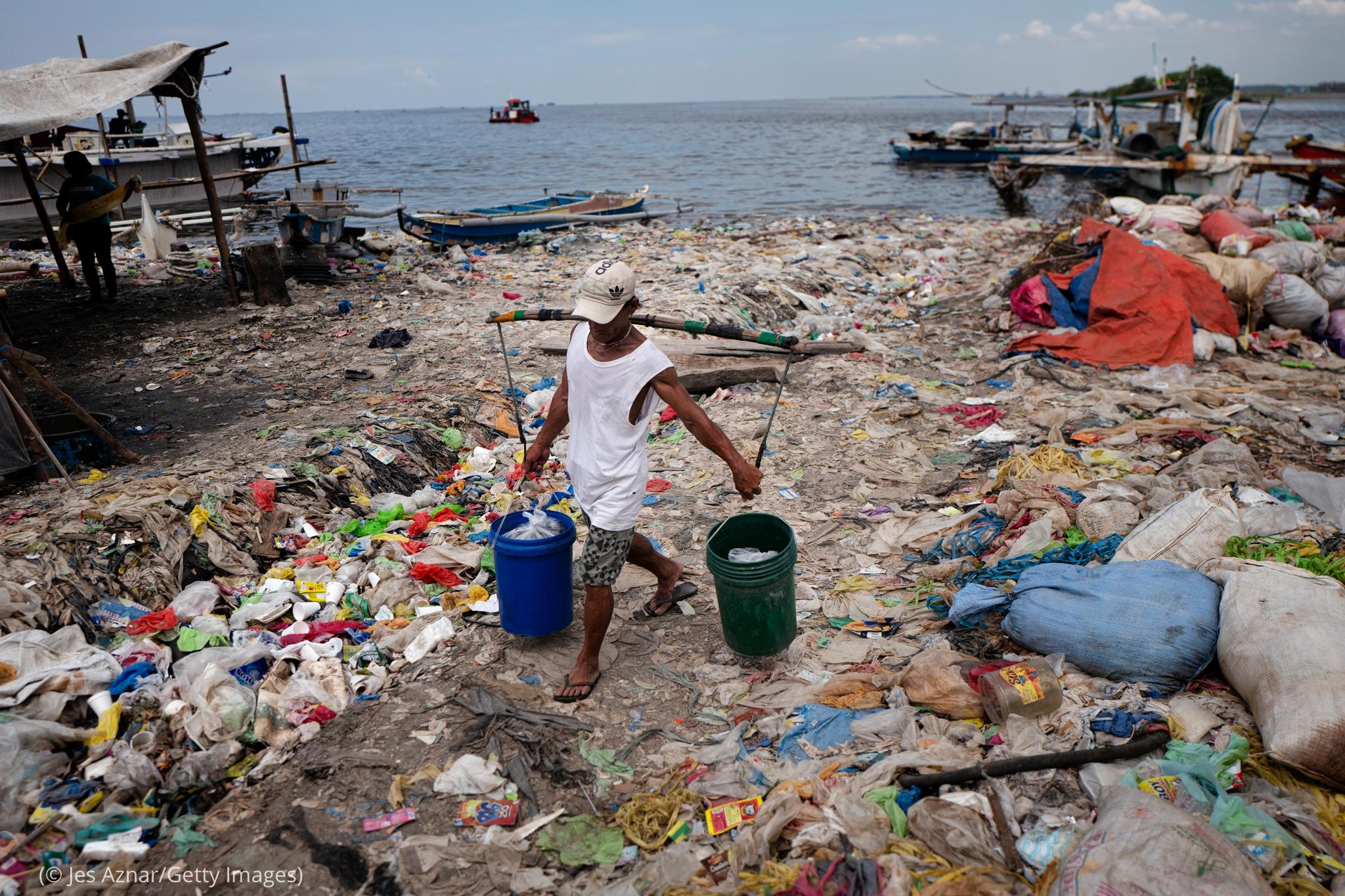 Un homme portant deux seaux et marchant sur une plage jonchée d'ordures (© Jes Aznar/Getty Images)