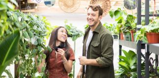 Smiling woman and man in greenhouse (© Tess Laureen Photography)