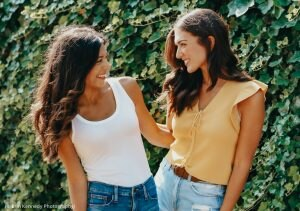 Two young women facing each other and smiling (© Erin Kennedy Photography)