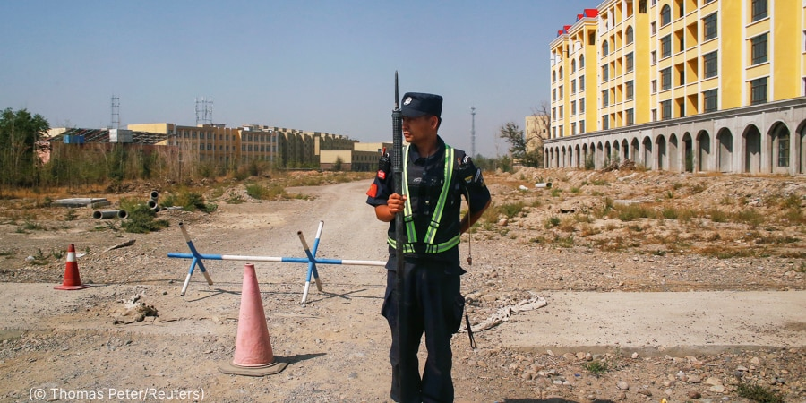 Homem de uniforme portando uma arma e parado em uma via de terra em frente a um edifício (© Thomas Peter/Reuters)