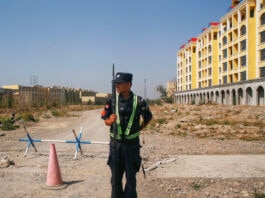 Man in uniform holding gun and standing on dirt road in front of building (© Thomas Peter/Reuters)