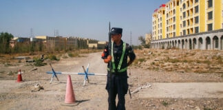 A Chinese police officer takes standing on dirt road in front of building
