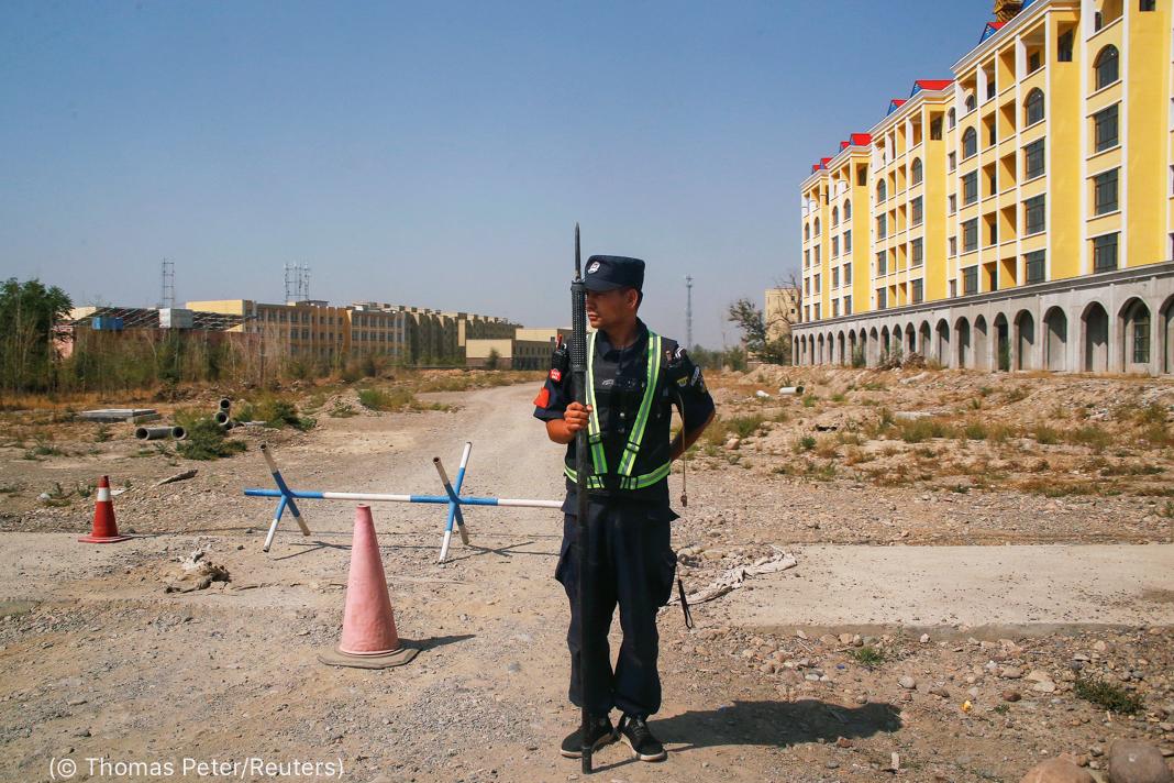 一名身穿制服的持枪男子站在一栋大楼前(© Thomas Peter/Reuters)