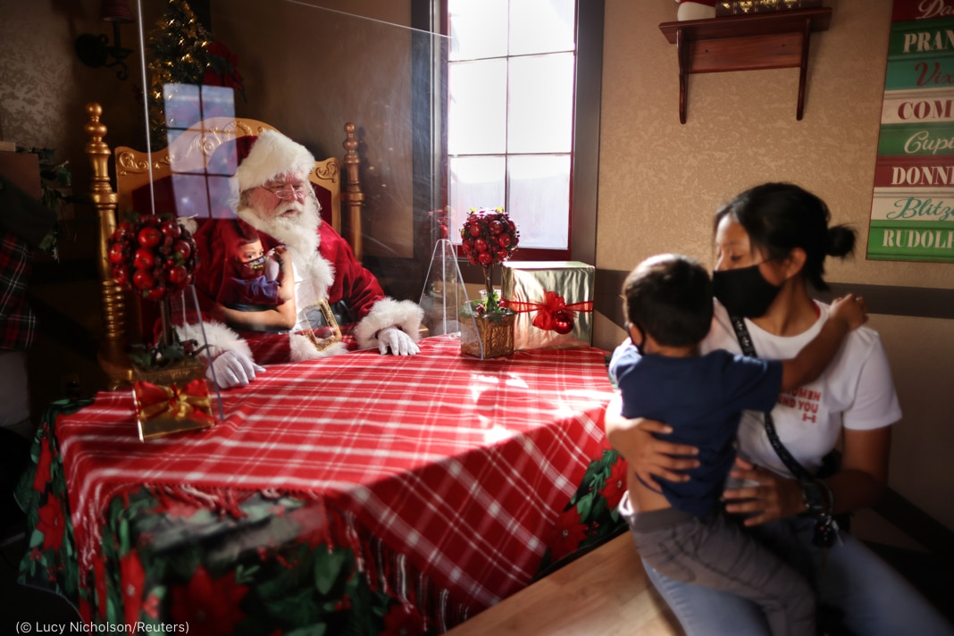 Santa Claus sitting behind plexiglass divider across table from woman holding child (© Lucy Nicholson/Reuters)