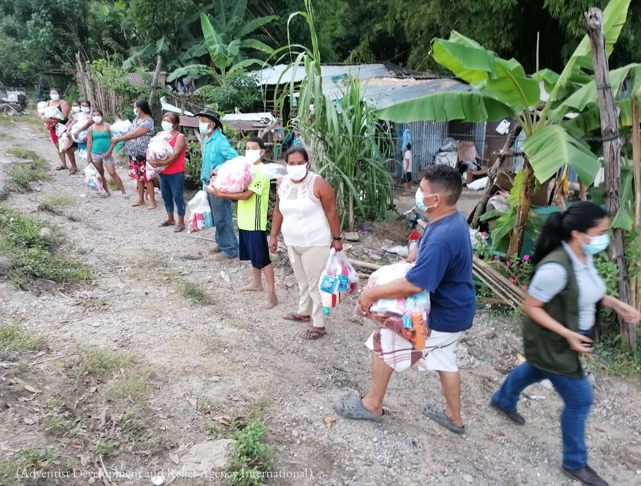 Line of people holding plastic bags of supplies (Adventist Development and Relief Agency International)