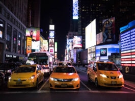 Taxicabs lined on a street with an LED American flag at right (