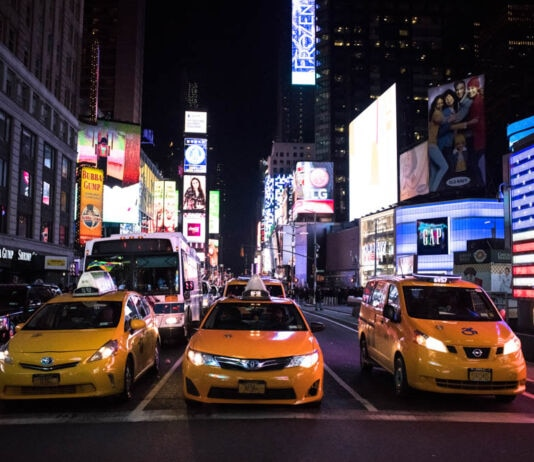 Taxicabs lined on city street at night (© Kholood Eid/The New York Times/Redux)