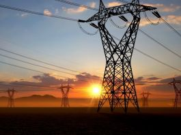 Sun rising behind electricity towers (© AP Images)