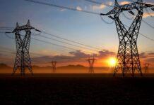 Vista de la salida del sol tras torres eléctricas (© AP Images)