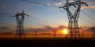 Sol nascendo atrás de torres de eletricidade (© AP Images)