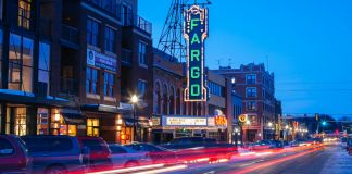 Street scene at dusk with car lights streaming past row of low buildings with a neon Fargo sign (© FiledIMAGE/Shutterstock)