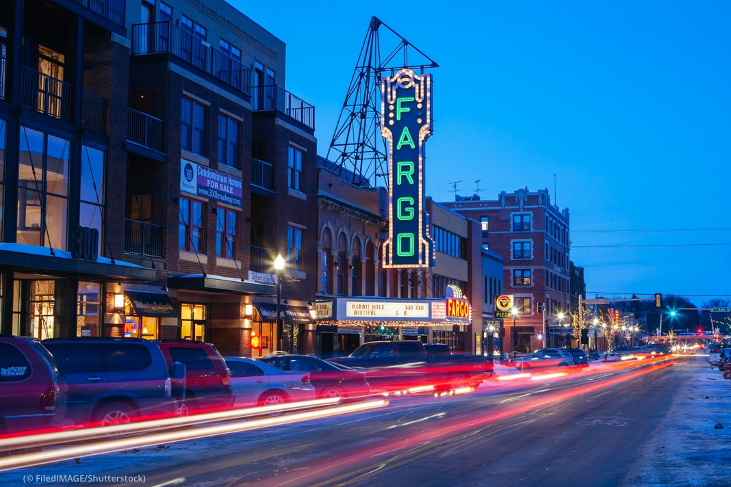 Street scene at dust with car lights streaming past and a neon Fargo sign (© FiledIMAGE/Shutterstock)