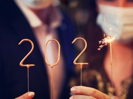 People holding numbers on sticks and a sparkler (© Kamil Macniak/Shutterstock)