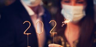 People holding numbers on sticks to form 2021, with sparkler for the 1 (© Kamil Macniak/Shutterstock)