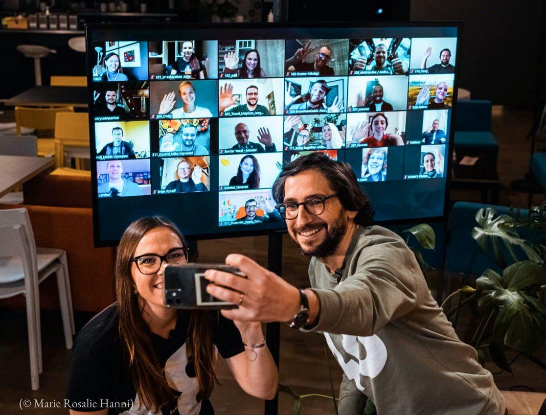 Une femme et un homme en train de prendre un selfie devant un grand écran (© Marie Rosalie Hanni)