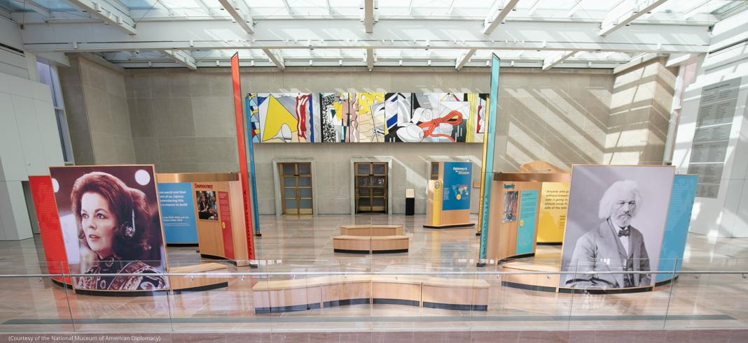 Galerie parsemée de bancs, avec de grandes photos au sol et des tableaux au mur (Photo offerte par le National Museum of American Diplomacy)