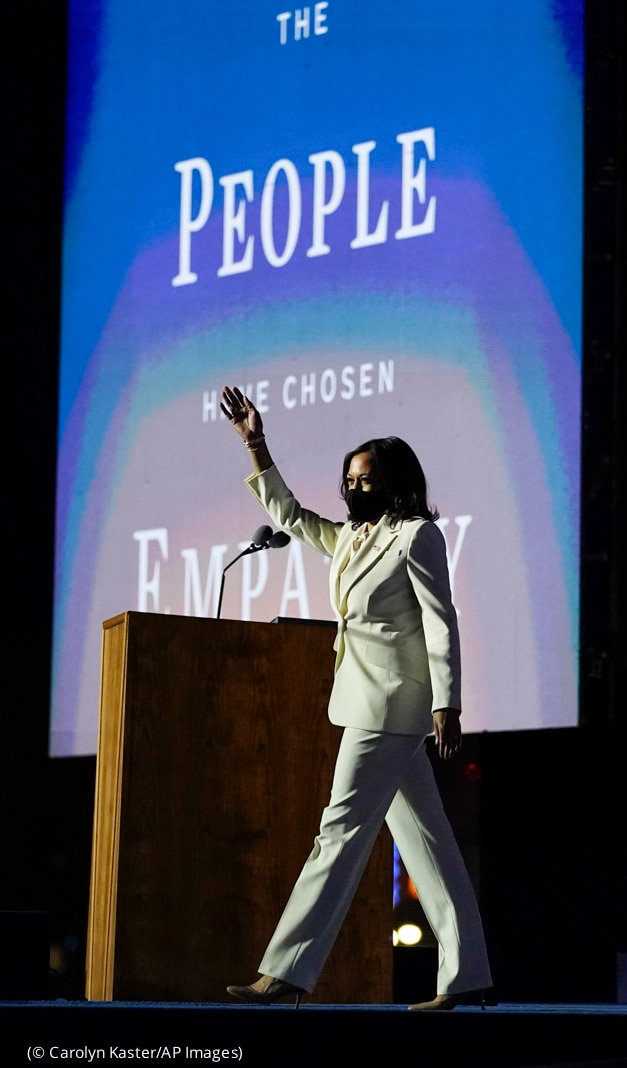 Kamala Harris, in white pantsuit, walking onto stage and waving, with lectern and large screen behind (© Carolyn Kaster/AP Images)