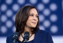 Kamala Harris standing in front of U.S. flag (© Nareshkumar Shaganti/Alamy)