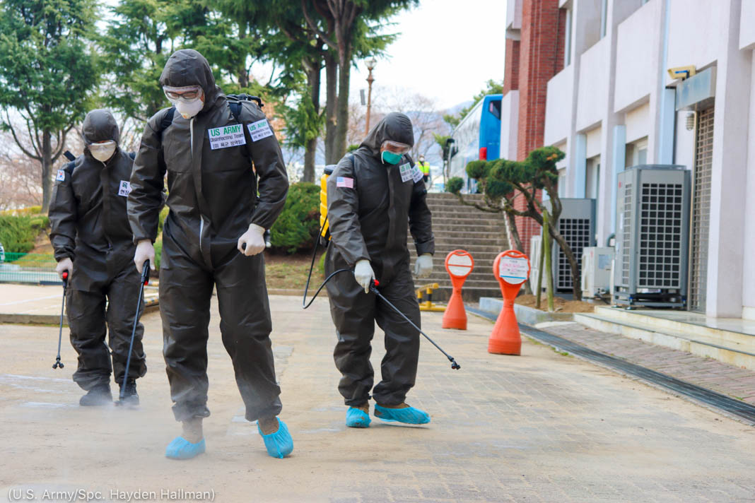 Three people in protective suits spraying concrete ground with disinfectant (U.S. Army/Spc. Hayden Hallman)