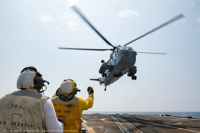 U.S. Navy personnel guide an Indian Navy helicopter in for landing (U.S. Navy/Mass Communication Specialist Seaman Drace Wilson)