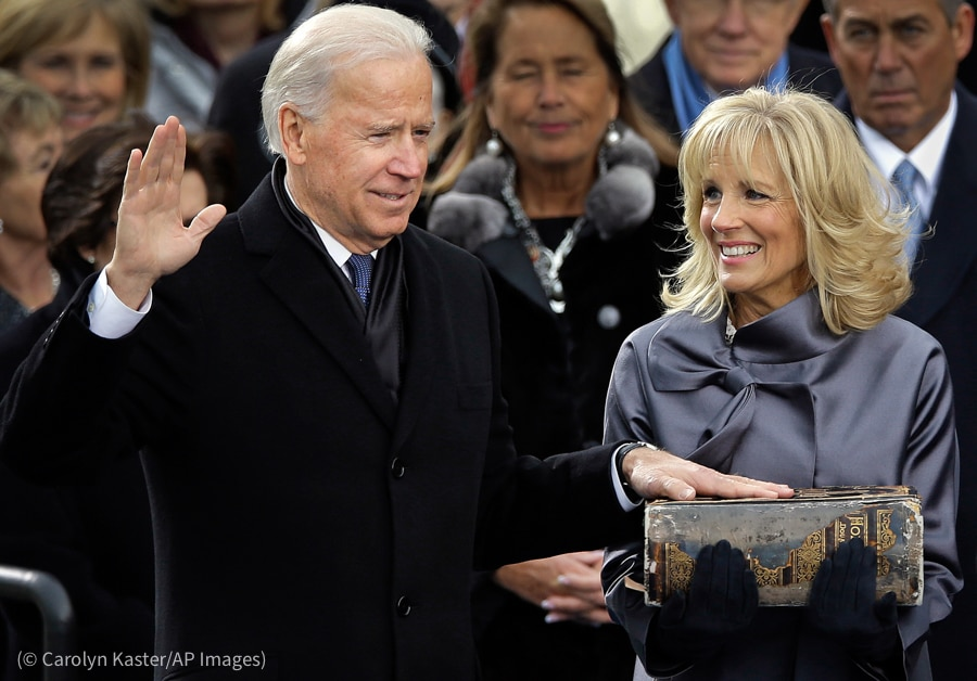 Joe Biden with right hand raised and left hand on large Bible held by Jill Biden (© Carolyn Kaster/AP Images)