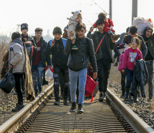 ریل کی پٹڑی کے ساتھ چلتے ہوئے لوگوں کا ایک گروپ