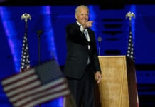 Joe Biden on stage, pointing, with U.S. flag in foreground (© Andrew Harnik/AP Images)