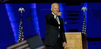 Joe Biden pointing the index finger of his right hand on stage with a U.S. flag in the foreground (© Andrew Harnik/AP Images)