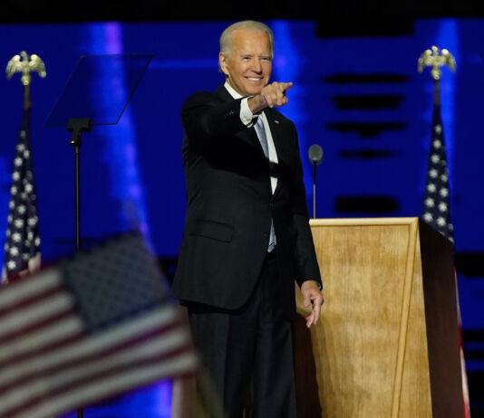 Joe Biden, sur une scène, devant un pupitre et des drapeaux, souriant et pointant quelqu'un du doigt (© Andrew Harnik/AP Images)