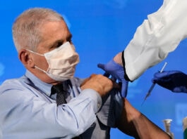 Man wearing surgical mask getting vaccination (©Patrick Semansky/AP Images)