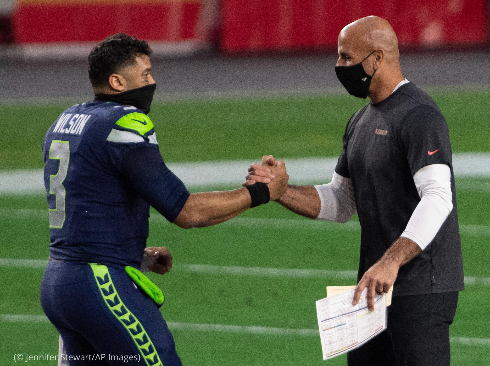 Two men shaking hands on football field (© Jennifer Stewart/AP Images)
