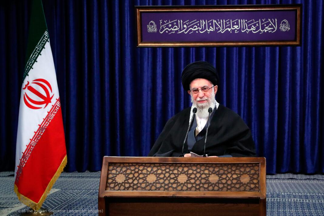 Ali Khameni s'exprimant sur un podium avec le drapeau iranien à gauche (© Office of the Iranian Supreme Leader/AP Images)