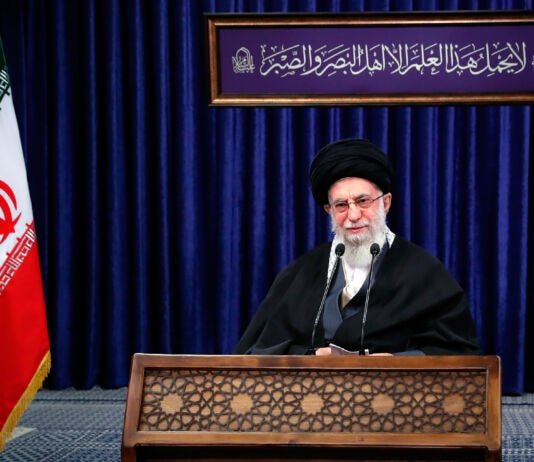 Ali Khamenei speaking on podium with an Iranian flag on the left (© Office of the Iranian Supreme Leader/AP Images)