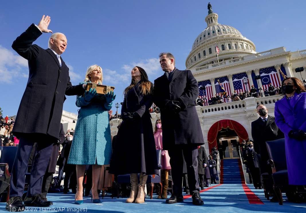 Joe Biden holding one hand up and one on Bible held by Jill Biden in front of U.S. Capitol as others look on (© Andrew Harnik/AP Images)