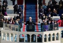 President Biden standing at lectern on stage balcony, flanked by seated people (AP Photo/Patrick Semansky, Pool)