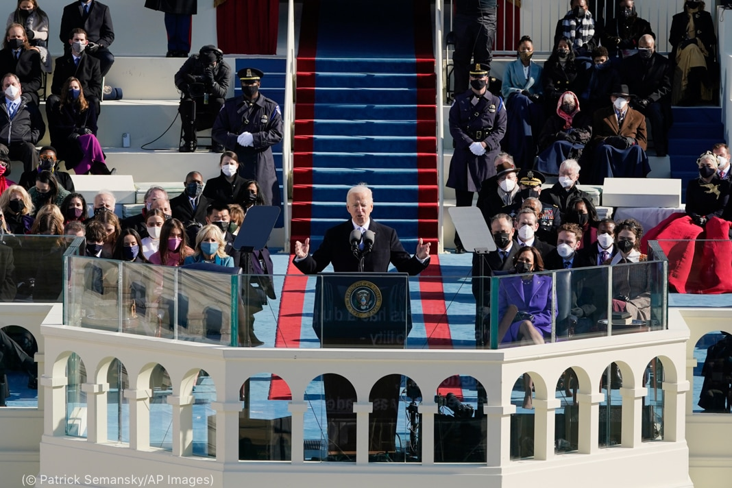 Joe Biden speaking at lectern with open arms as inaugural attendees look on (© Patrick Semansky/AP Images)