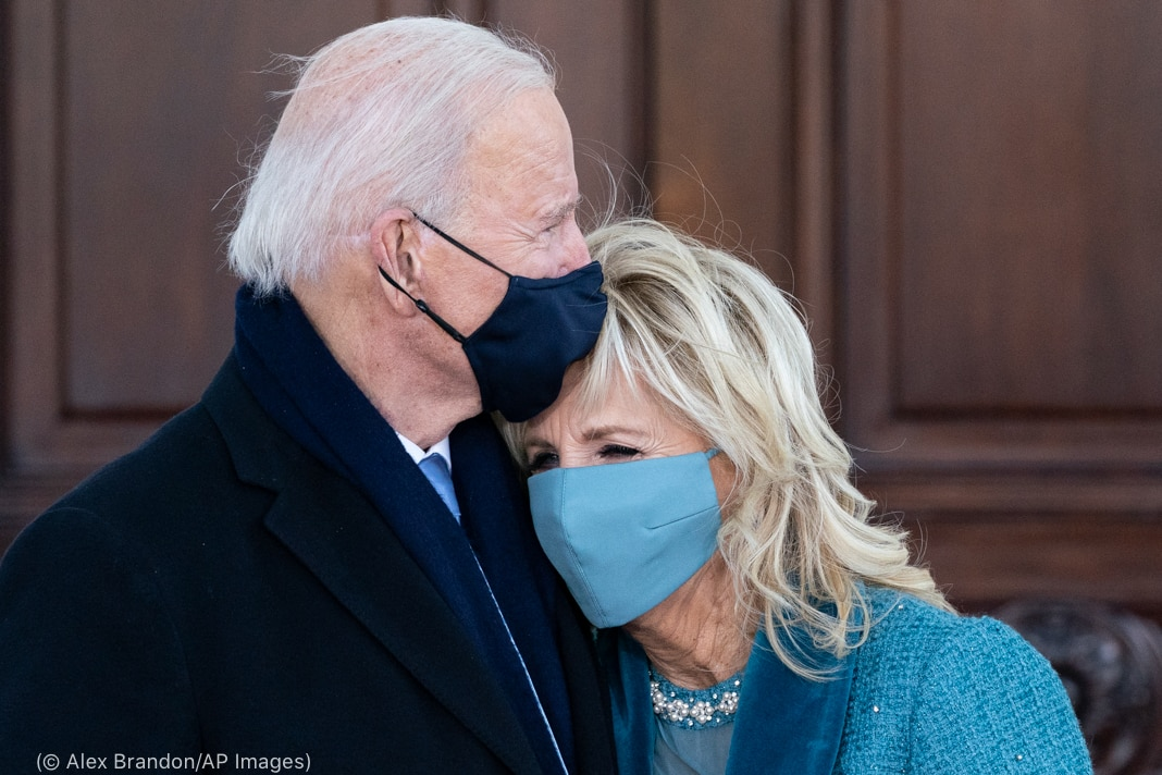 Jill Biden resting head on Joe Biden's shoulder in front of large wooden door (© Alex Brandon/AP Images)