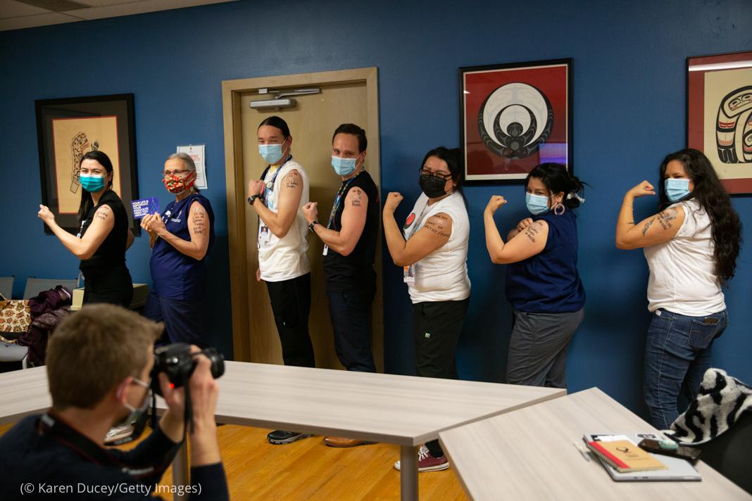 Fila de mulheres e homens mostrando o braço depois de receberem a vacina para Covid-19 (© Karen Ducey/Getty Images)