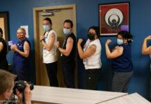 کووڈ-19 کی ویکسین لگوانے والی عورتیں اور مرد اپنے بازو دکھا رہے ہیں (© Karen Ducey/Getty Images)