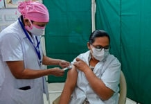 Health worker administering injection to woman (© Sam Panthaky/AFP/Getty Images)