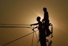 2 silhouetted men standing at the top of electricity poles (©