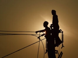 Two silhouetted men standing at top of utility pole (© Sanjay Kanojia/AFP/Getty Images)